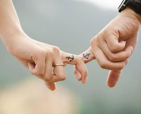 Ein Paar hat zwei Finger ineinander verschränkt. Auf den Fingern sind Anker tätowiert.