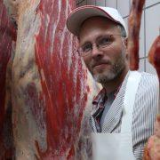 Ein Mann steht umgeben von Fleisch an Haken.