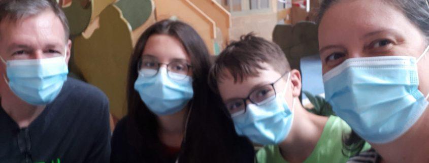 Eine Familie sitzt mit Mundschutz nebeneinander.