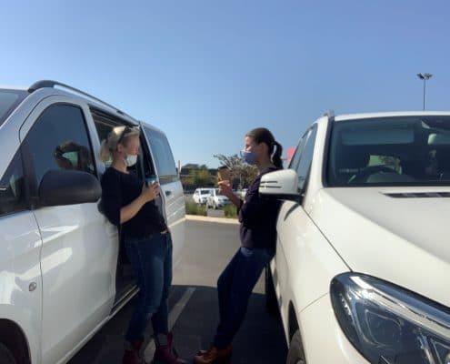 Zwei Menschen stehen sich an Autos gelehnt gegenüber.