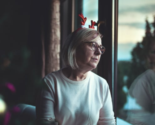 Eine Frau mit einem Deko-Geweih auf dem Kopf starrt aus dem Fenster.