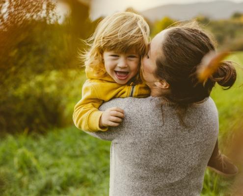 Eine Frau hält ein Kind in den Armen. Das Kind lächelt.